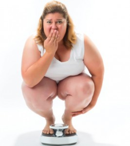 Obese young woman crouching on a scale